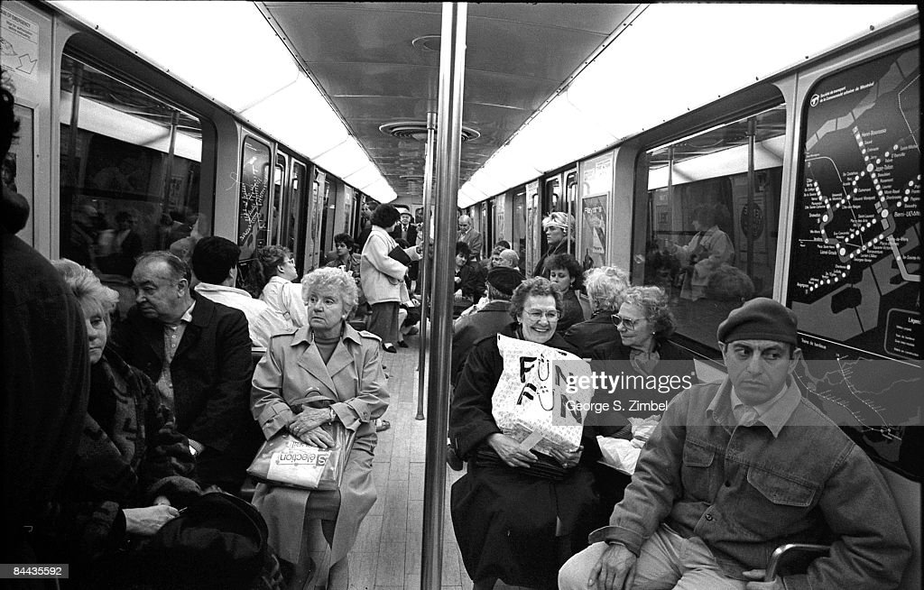 A woman smiles as she holds a shopping bag with a logo that reads 'Fun Fun' on her lap, Montreal, 1986. Other passengers of the Montreal Metro can be seen within the car.