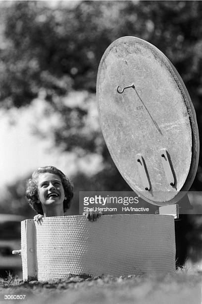 A woman smiles as she looks out from the entrance to an underground bomb fallout shelter Texas 1961