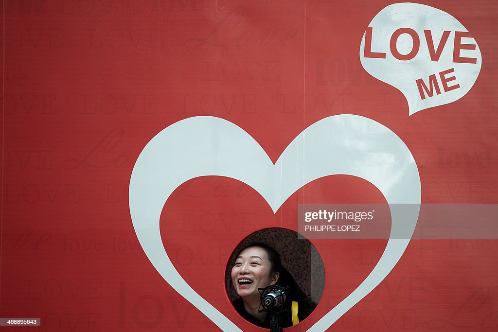 A woman smiles as she poses for a picture by a Valentine's Day cut-out displayed outside a shopping mall in Hong Kong on February 12, 2014. Businesses in China are specially looking forward to this year Valentine's Day on February 14 as it falls on the same day of the Chinese Lantern Festival, also known as Chinese Valentine's Day, which according to the Chinese calendar happens only every 19 years. AFP PHOTO / Philippe Lopez
