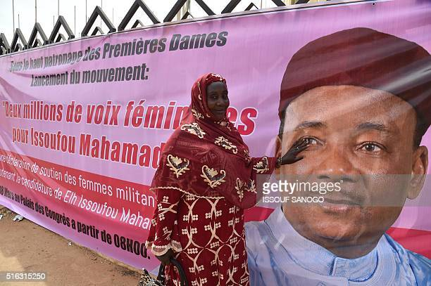 A woman smiles as she poses next to the electoral banner of Niger's incumbent President and candidate to his reelection Mahamadou Issoufou in Niamey...