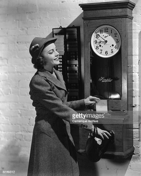 A woman smiles as she puts her timecard into a punch clock to begin her work day She wears an overcoat and a hat with a feather Other employee...