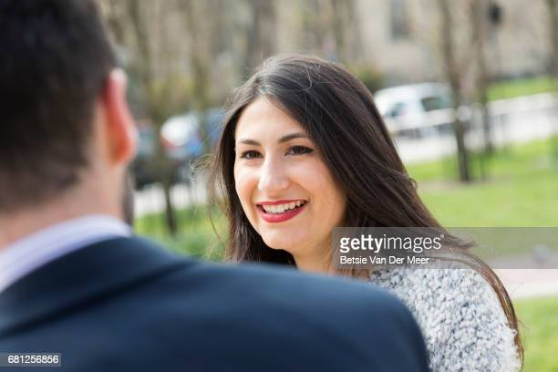 Woman smiles at friend while walking in city square.