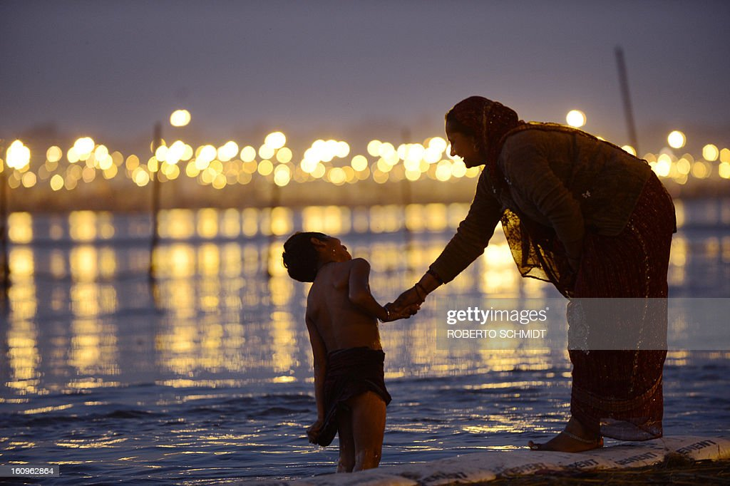 A woman smiles at her son as she holds him while he bathes in the waters of Sangam or confluence of the Yamuna, Ganges and mythical Sarawati rivers at sunset during the Maha Kumbh festival in Allahabad on February 8, 2013. The Kumbh Mela in the town of Allahabad will see up to 100 million worshippers gather over 55 days to take a ritual bath in the holy waters, believed to cleanse sins and bestow blessings.