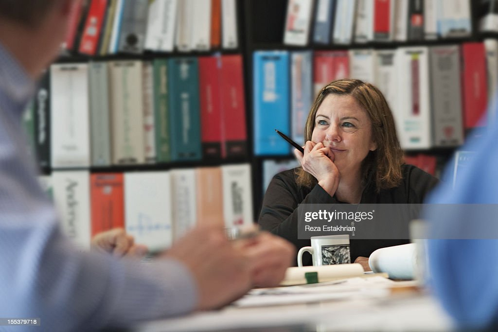 Woman smiles during meeting : Stock Photo