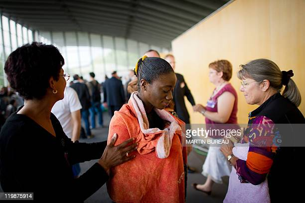A woman smiles gets out of the water after being baptised during a Jehovah's Witnesses assembly gathering 30000 believers on July 23 2011 in...
