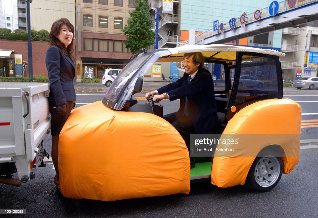 A woman smiles though getting stucked between a track and 'iSAVE YOU', electric vehicle covered with shock absorbing air-bag type material, during its revealing on November 15, 2012 in Hiroshima, Japan. Humanix, Hiroshima University affiliated venture company have developed the EV, and now the company accept orders at the price of 790,000 Japanese yen, or 9,772 U.S. dollars.