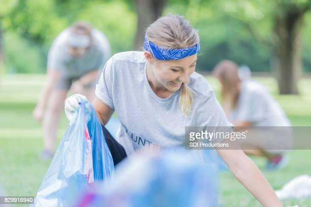 Sourires de femme tout en aidant les voisins pendant le nettoyage de la communauté
