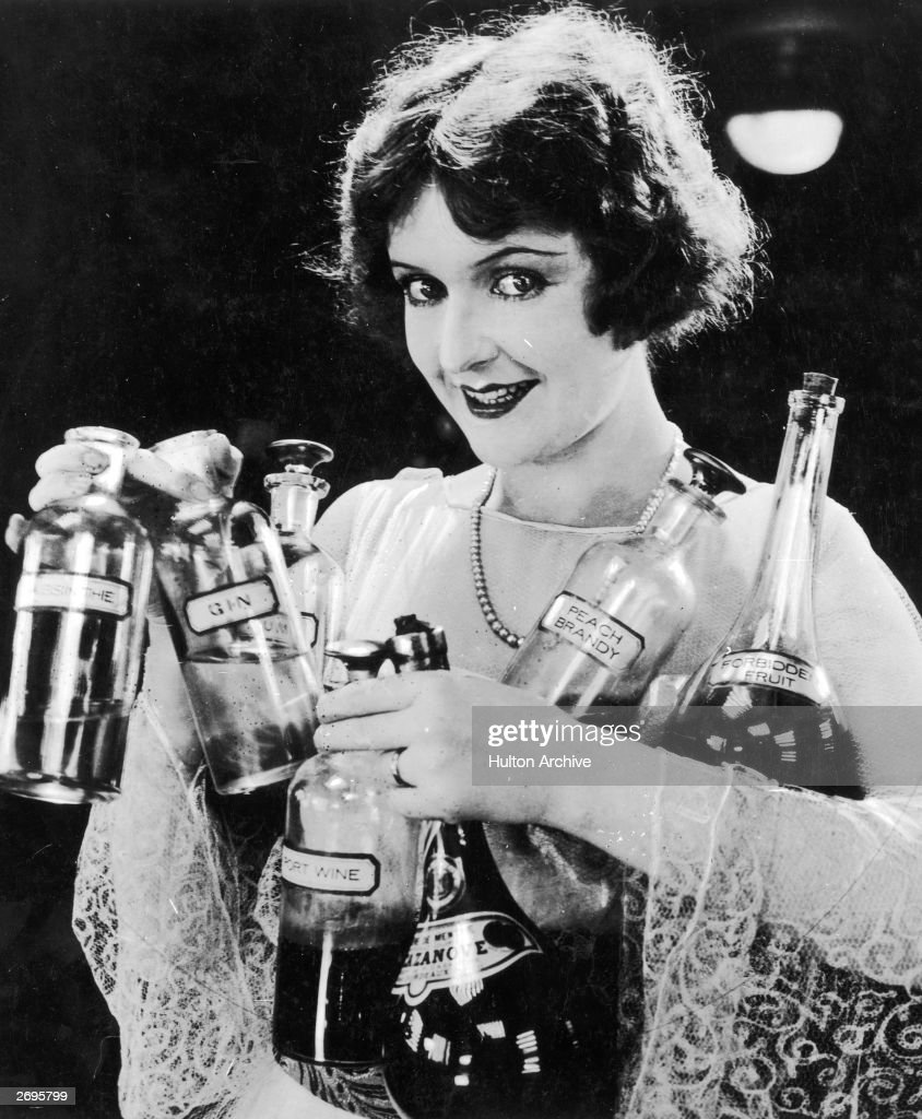 A woman smiles while holding bottles of various types of alcohol including peach brandy port wine gin absinthe and forbidden fruit