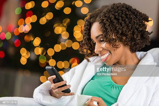 Woman smiling after receiving text message on Christmas morning