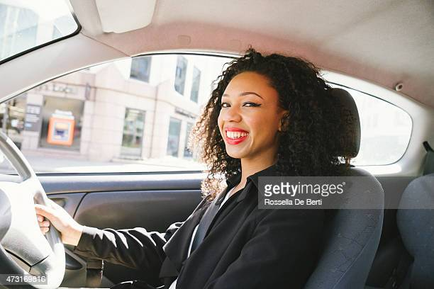 Woman smiling and driving a car