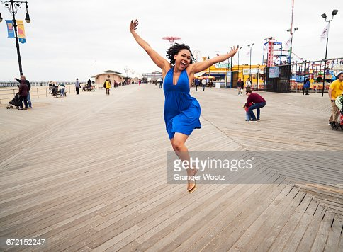 Woman smiling and jumping on boardwalk at amusement park
