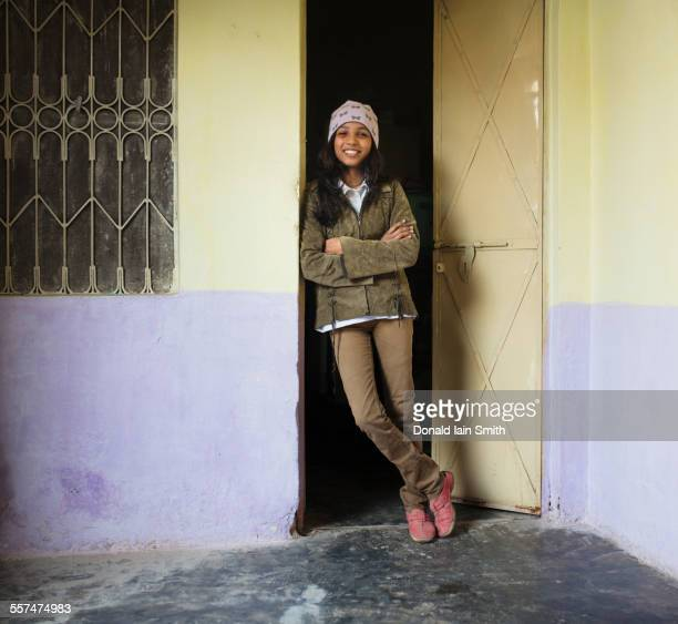 Woman smiling and leaning in doorway