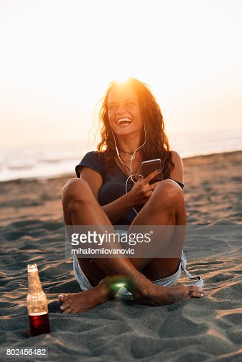 Woman smiling and listening to music : Stock Photo