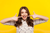 Cheerful girl pointing on her opened mouth and looking at camera on the yellow background.