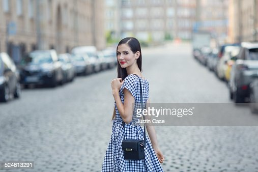 woman smiling and turning back at us in the street