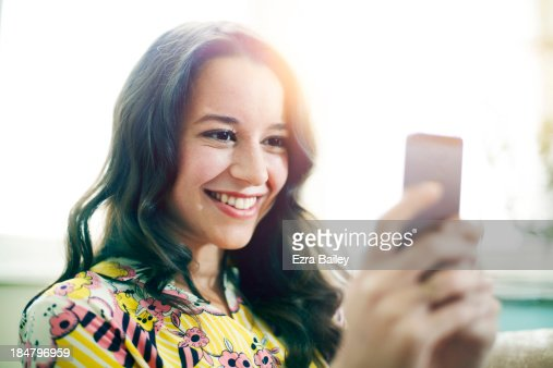Woman smiling and using her mobile phone. : Stock Photo