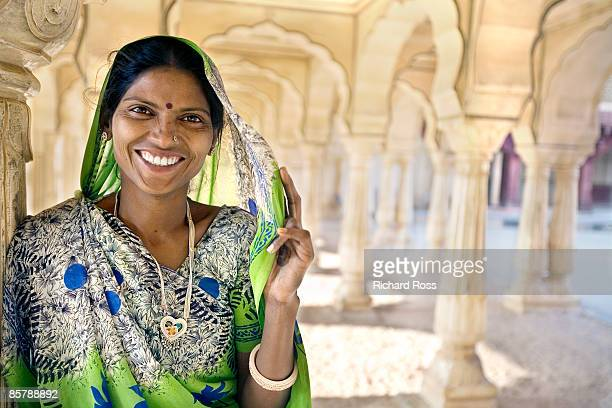 A woman smiling and wearing a green sari