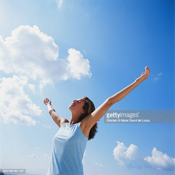 Woman smiling, arms outstretched, low angle view