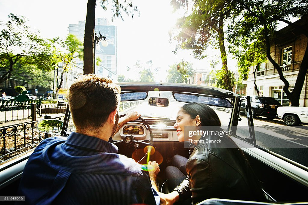 Woman smiling at boyfriend driving convertible on city boulevard