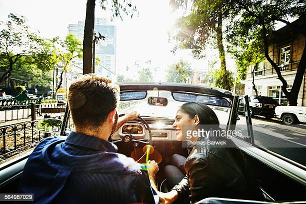 Woman smiling at boyfriend driving convertible