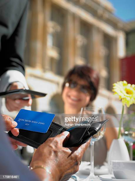 Woman smiling at friend making credit card payment