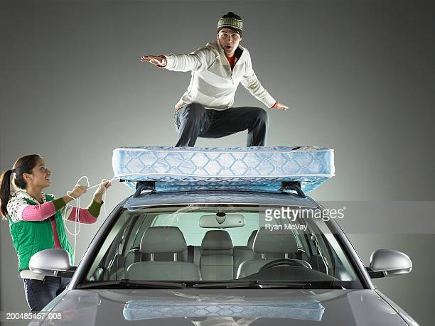 Woman smiling at man standing atop mattress on car roof