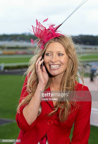 Woman smiling at the races using mobeil phone
