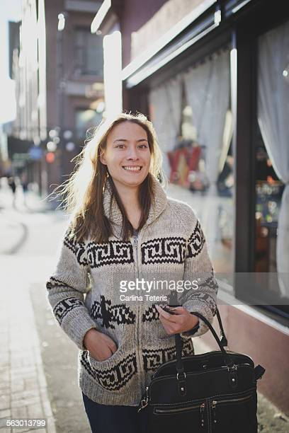 Woman smiling awkwardly, shopping on a cold day