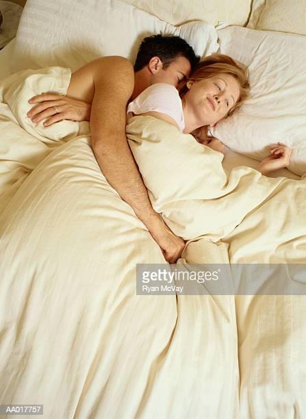 Woman Smiling Beside Her Sleeping Husband