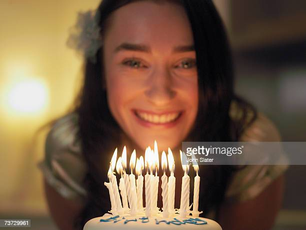 'Woman smiling by birthday cake with candles, focus on candles'