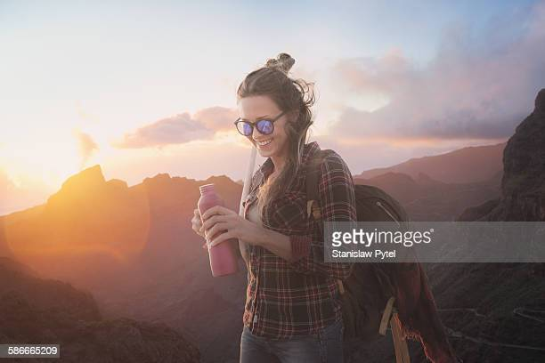 Woman smiling, drinking water in mountains