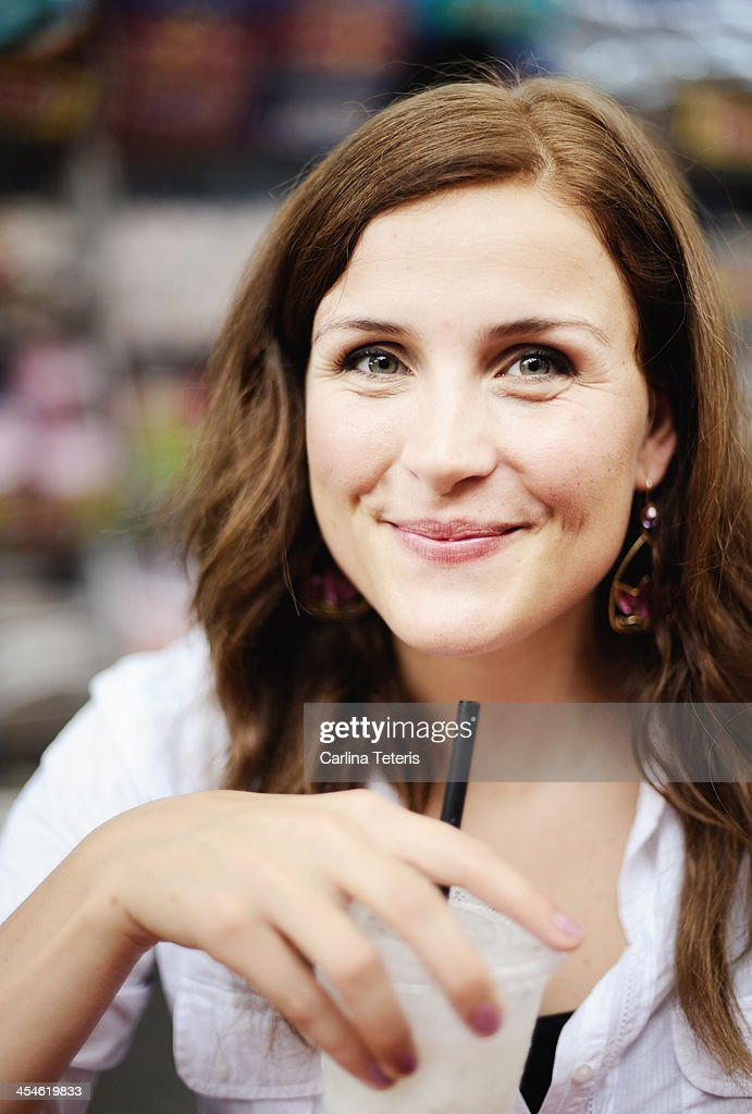 Woman smiling holding a glass of juice : Stock Photo