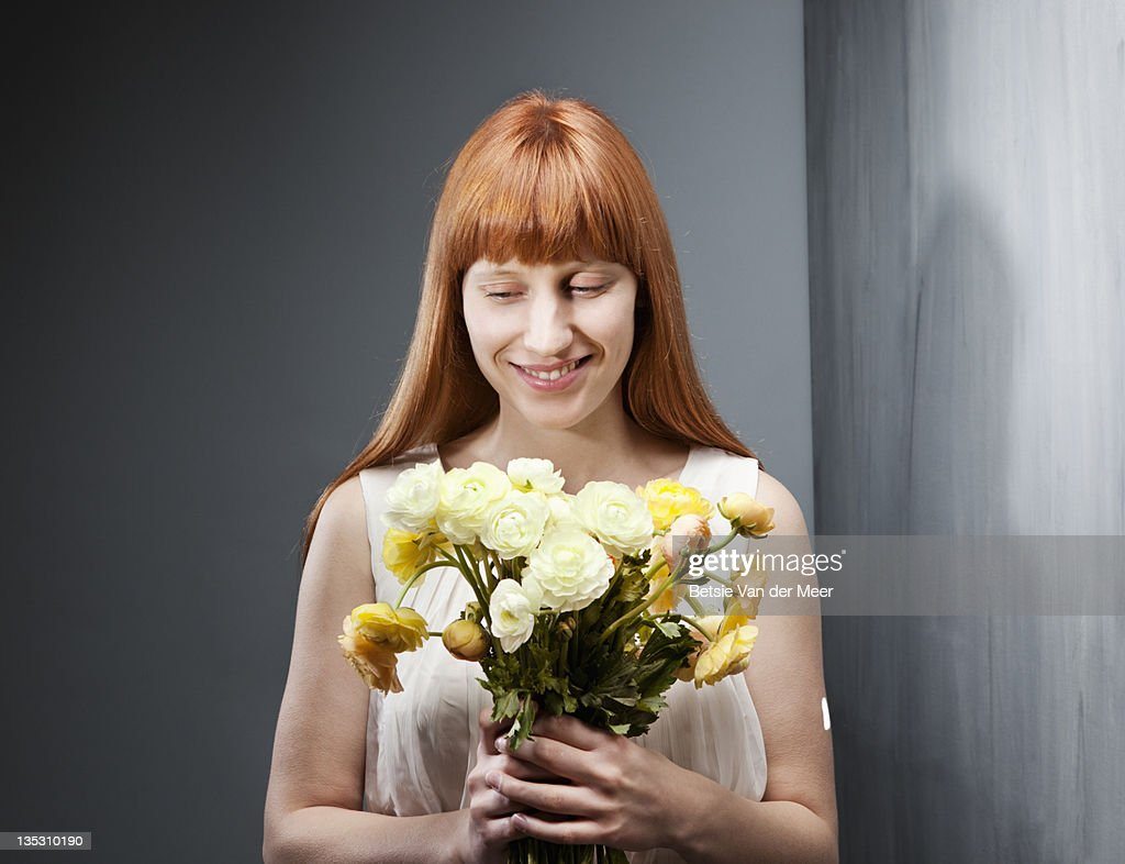 Woman smiling, holding bouquet of flowers. : Stock Photo