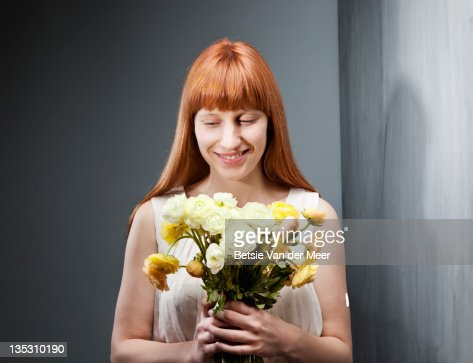 Woman smiling, holding bouquet of flowers. : Foto de stock
