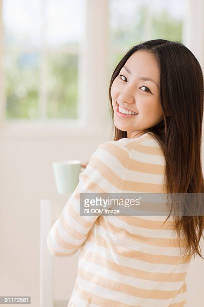Woman smiling, holding mug
