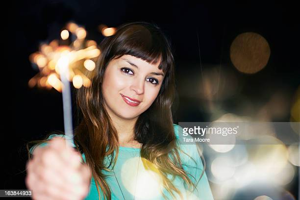 woman smiling holding sparklers up to camera