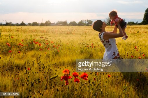 Woman smiling in a poppy field with her babby girl. : Stock-Foto