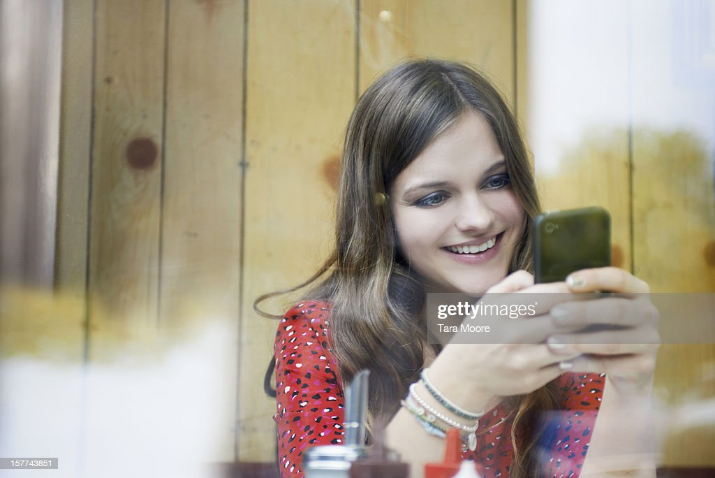 woman smiling in cafe and texting on phone : Stock Photo
