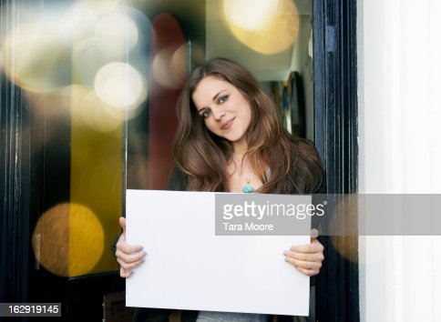 woman smiling in doorway with blank sign
