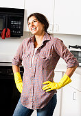 Woman smiling in kitchen, cleaning