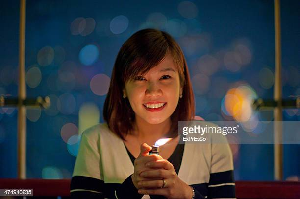 A woman smiling in n front of the Christmas lights