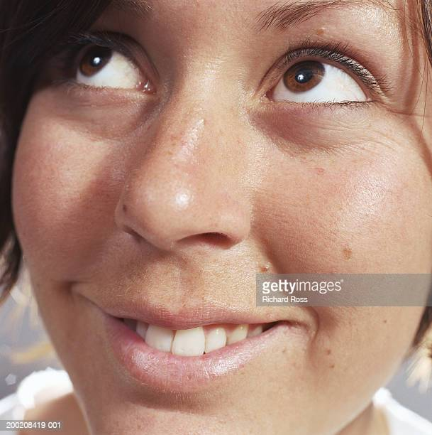 Woman smiling, looking up and to side, close-up