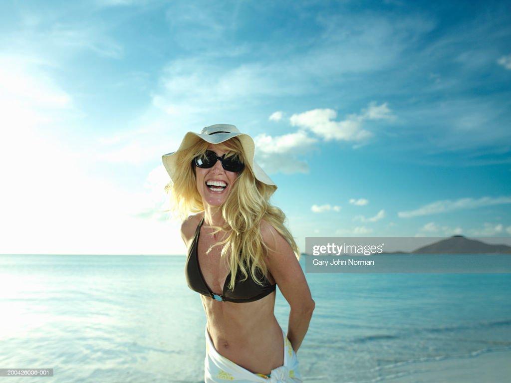 Woman smiling on beach, portrait