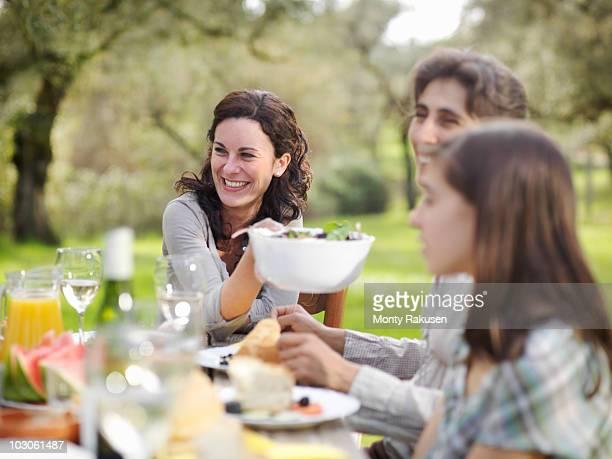Woman smiling, passing salad bowl