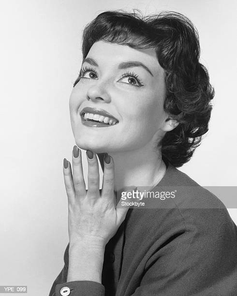 Woman smiling, posing with hand under chin