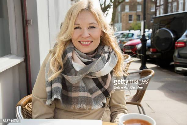 Woman smiling, sitting in outdoor cafe in city.