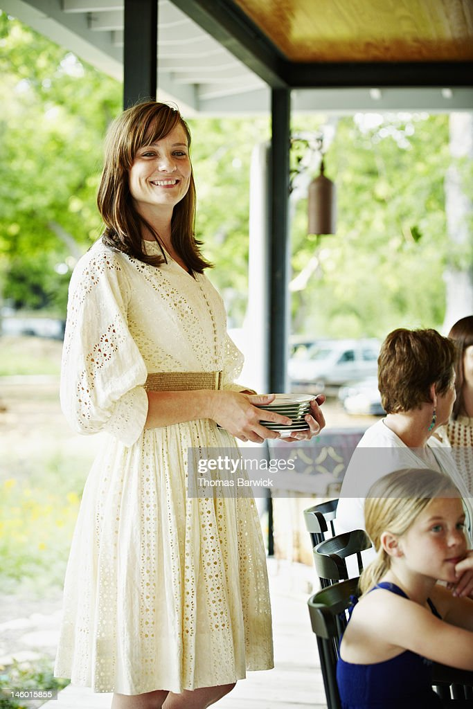 Woman smiling standing holding stack of plates : Stock Photo