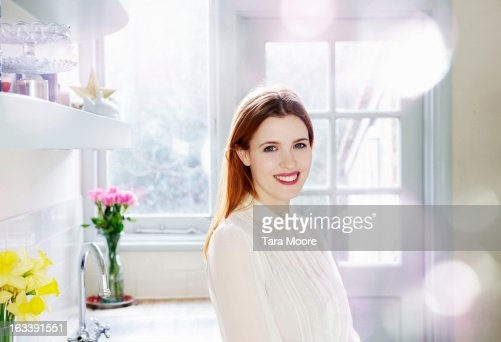 woman smiling to camera in kitchen in morning : Stock Photo