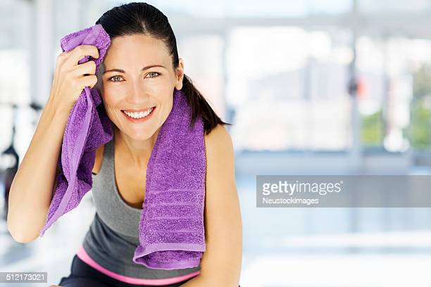 Woman Smiling While Cleaning Sweat From Forehead In Gym