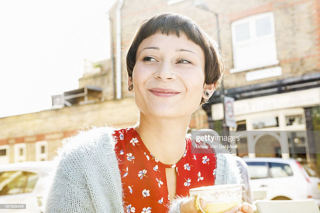 Woman smiling while drinking tea in outdoor cafe.